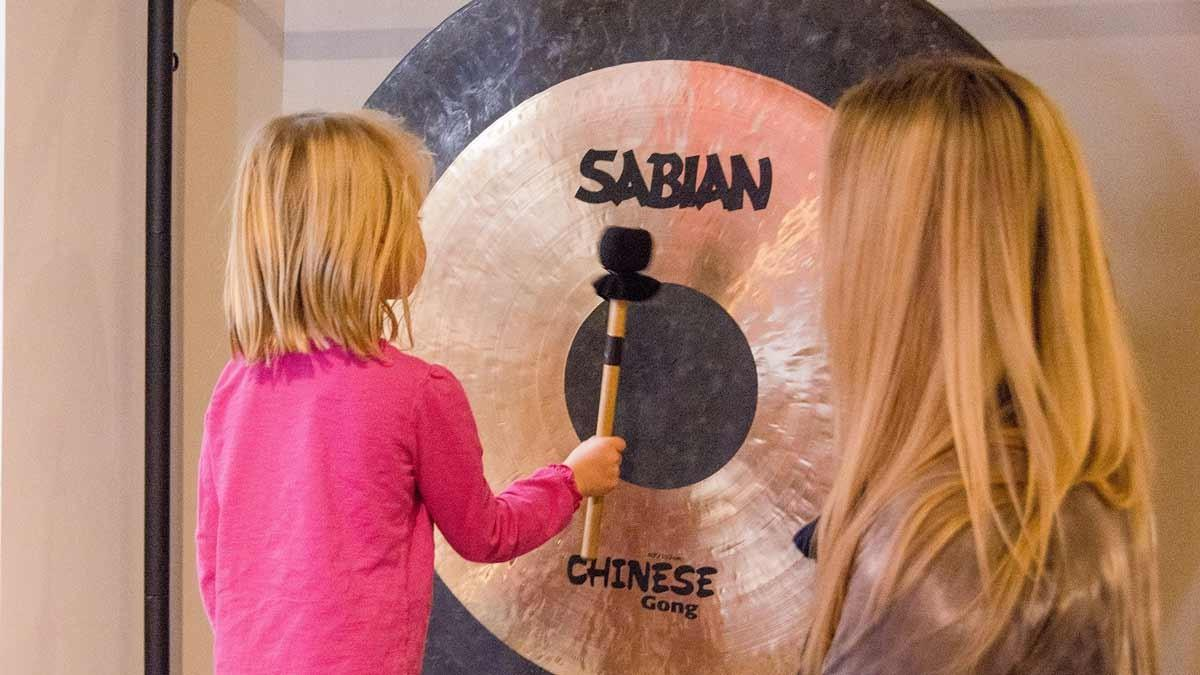 A Child Playing a Large Gong